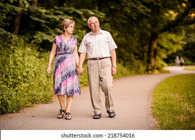Happy senior couple walking together holding hands in forest park