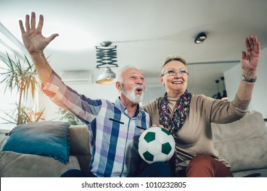 Happy senior couple watching soccer on tv and celebrating victory at home
