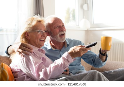 Happy senior couple watching television at home, sitting on sofa covered with blanket