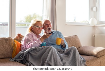 Happy senior couple watching television at home, sitting on sofa, covered with blanket