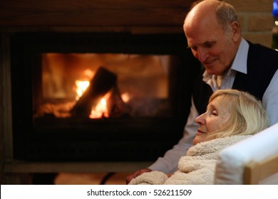 Happy senior couple, wrapped in warm knitted plaid, relaxing at home in the living room, sitting in rocking chair by fireplace and enjoying cosy evening together - successful retirement concept