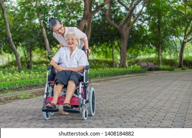 Happy senior daughter and her mother in wheelchair are smiling and laughing in garden. They are Asian peoples in Thailand.