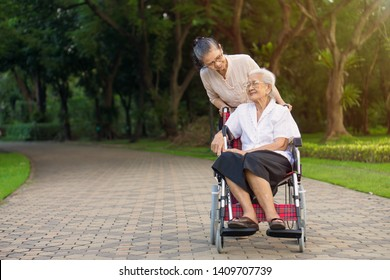 Happy senior daughter and her mother in wheelchair are smiling in public park. They are Asian peoples in Thailand.