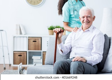 Happy senior disabled man with walking stick and caring young nurse