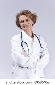 Happy senior doctor smiling (isolated on gray)