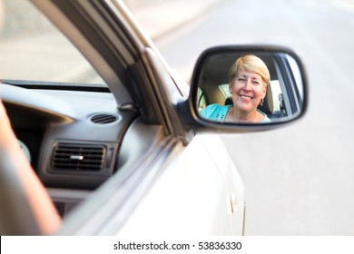 happy senior driver looking at side mirror