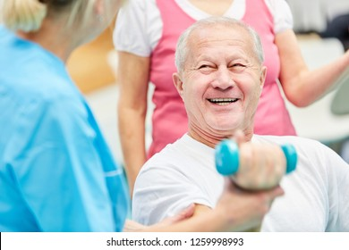 Happy senior in dumbbell training in physiotherapy with care