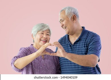 Happy senior elderly man and woman couple smiling isolated on pink background, looking at each other, with hands in form of heart