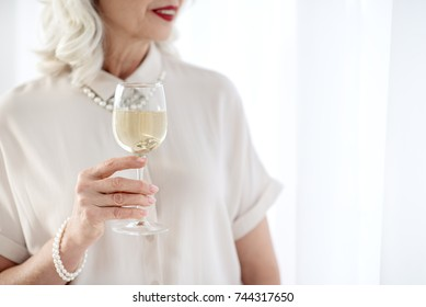 Happy senior elegant woman drinking champagne