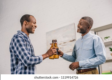 happy senior father and adult son clinking beer bottles and smiling each other at home