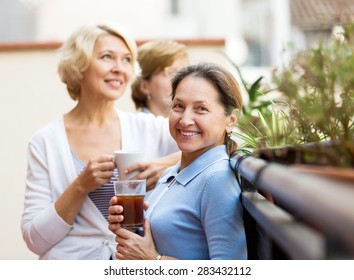 Happy senior female colleagues having lunch break at patio and drinking tea