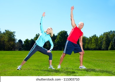 Happy senior fitness couple in the park.