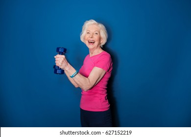 Happy senior fitness woman training with dumbbells isolated on blue