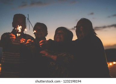 Happy senior friends celebrating birthday with sparklers stars outdoor - Older people having  fun in terrace in the summer nights - Concept of friendship, pensioners and retirement