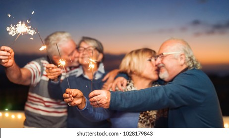 Happy senior friends celebrating with sparklers outdoor - Older people having a fun and tender moment on rooftop - Love, party, elderly lifestyle concept