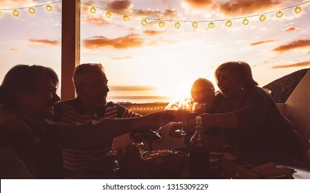Happy senior friends cheering and toasting with red wine at terrace dinner - Mature people having fun dining together on rooftop at sunset - Friendship, food and drink, elderly lifestyle concept
