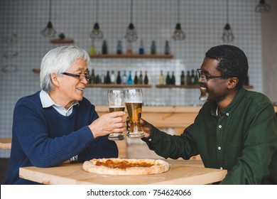 happy senior friends clinking glasses of beer at bar with pizza on table