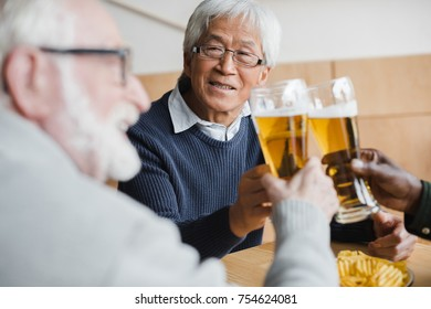 happy senior friends clinking glasses of beer while having meeting