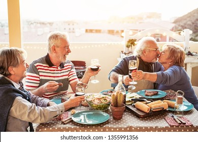 Happy senior friends dining and cheering with red wine at barbecue in terrace outdoor - Retired people having fun at bbq party on patio - Friendship, food and elderly lifestyle concept