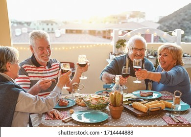 Happy senior friends dining and drinking red wine on house terrace - Mature people having fun laughing together at dinner party - Food and elderly friendship lifestyle concept