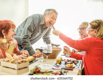 Happy senior friends having barbecue lunch at home - Old people having fun eating tasty meat skewers at bbq meal - Joyful elderly active lifestyle concept - Focus on left man face - Contrast filter