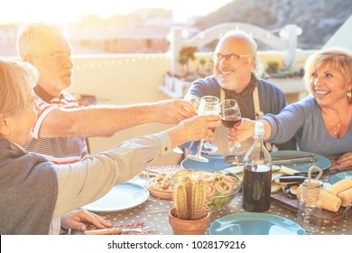 Happy senior friends having fun cheering with red wine at barbecue in terrace outdoor - Older people making  dinner toasting glasses and laughing together - Friendship and elderly lifestyle concept