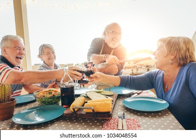 Happy senior friends having fun cheering with red wine at barbecue in terrace outdoor - Older people dining with grill meat and laughing together - Friendship and elderly lifestyle concept