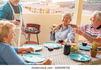 Happy senior friends having fun at barbecue dinner in patio outdoor - Mature old people dining and drinking wine at bbq meal - Focus on right woman face - Joyful elderly lifestyle and summer concept
