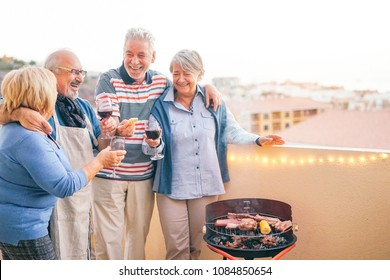 Happy senior friends having fun drinking red wine at barbecue dinner in terrace - Mature people dining and laughing together on rooftop - Friendship and elderly lifestyle concept