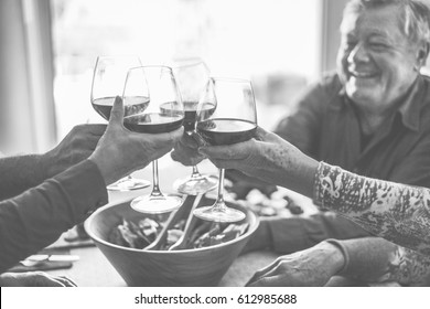 Happy senior friends having fun cheering with red wine - Mature people eating at dinner and laughing together - Black and white editing - Focus on bottom right hand - Joyful elderly lifestyle concept