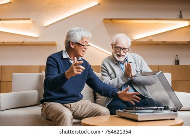 happy senior friends listening vinyl record while sitting on couch