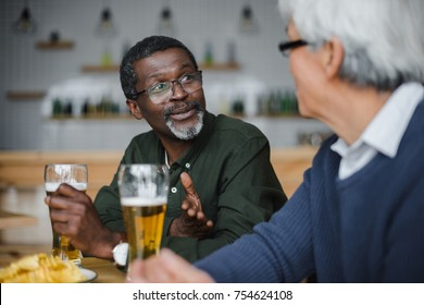 happy senior friends talking and drinking beer with chips at bar
