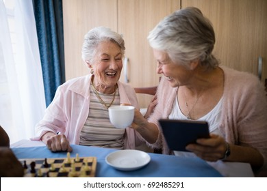 Happy senior friends talking while having coffee and playing chess at nursing home
