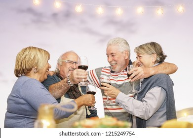 Happy senior friends toasting with red wine at barbecue dinner in terrace - Mature people dining and cheering together drinking wine on rooftop - Friendship and elderly lifestyle concept