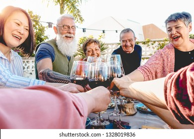 Happy senior friends toasting with red wine glasses at dinner on patio - Mature people having fun dining together outside - Elderly lifestyle, food and drink, retired and pensioners concept