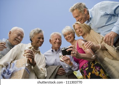 Happy senior friends watching their recorded moments together