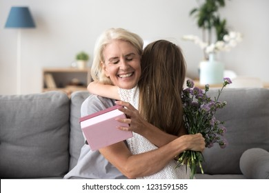 Happy senior grandma hugging granddaughter thanking for present holding flower bouquet, smiling excited old grandmother embracing little grandchild girl congratulating granny giving birthday gift box