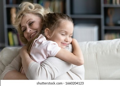 Happy senior grandmother sit on couch in living room hugging cute little preschooler granddaughter, smiling mature 70s granny embrace cuddle with small grandchild, show love and care, bonding concept