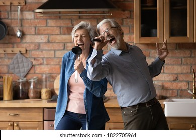Happy senior husband and wife have fun sing in kitchen appliances cooking together at home. Overjoyed mature grey-haired Caucasian couple feel energetic active enjoy family retirement weekend.