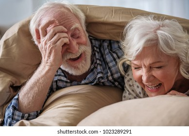 Happy senior husband and wife lying in bed. They are looking out from under the blanket in bedroom and laughing