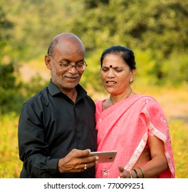 Happy senior Indian couple husband and wife using smartphone, looking at  photos on smartphone, smiling together at outdoor.