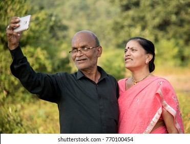 Happy senior Indian couple husband and wife taking a selfie on smartphone, smiling together at outdoor.