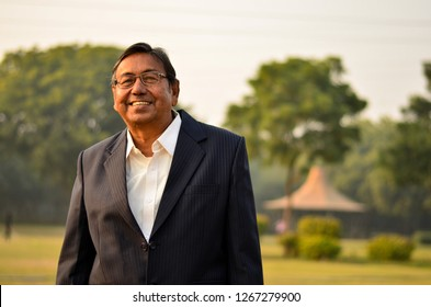 Happy senior Indian man wearing a suit standing and smiling in a park in New Delhi, India