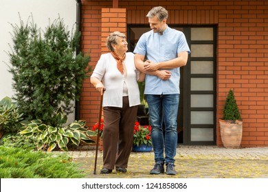 Happy senior lady with walking stick going for at walk with handsome male nurse