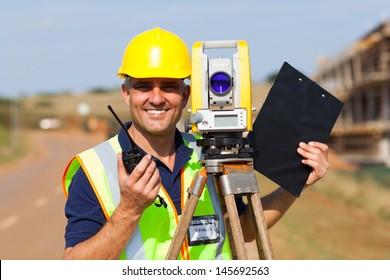 happy senior land surveyor with tacheometer on construction site