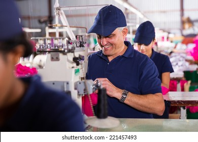 happy senior machinist sewing in clothing factory