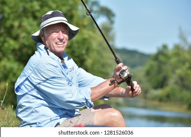 Happy Senior Male Fisherman With Fishing Rod Fishing