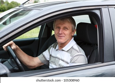 Happy senior male sitting in car on driver seat and smiling