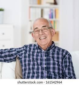 Happy senior man with a beaming smile wearing glasses sitting back relaxing in a chair at home
