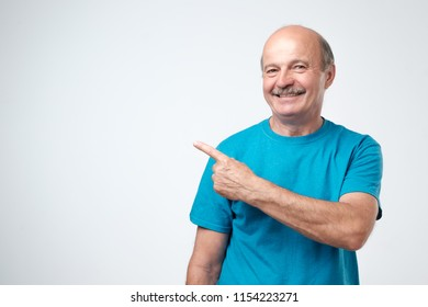 Happy senior man in blue tshirt looking at camera, smiling and pointing aside with hand. Copy space for text.